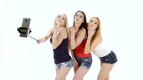 Brunette, redhead and blonde girl make selfie photo. White background stock video