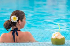 Brunette relaxes in the pool, standing near a coconut Royalty Free Stock Photos