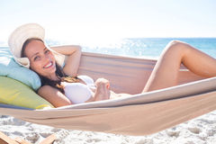 Brunette relaxing in the hammock and smiling at camera Royalty Free Stock Photos
