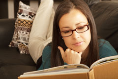 Brunette relaxing at home with book. Stock Photos