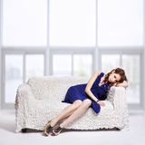 Brunette relaxing on sofa Royalty Free Stock Image