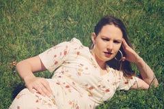 Brunette resting in park on the grass Stock Photo