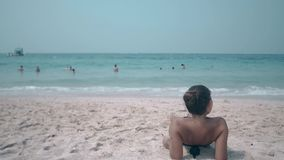 Brunette rests on sandy beach on sunny summer day backside. Wonderful brunette rests on sandy beach against boundless azure ocean on sunny summer day backside stock video
