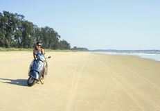 Brunette rides on a deserted beach along the ocean at mot. Tanned brunette rides on a deserted beach along the ocean at motorcycle Stock Photo
