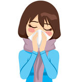 Brunette Runny Nose. Beautiful woman wearing a warm scarf suffering influenza and runny nose blowing her nose with a handkerchief Royalty Free Stock Photography