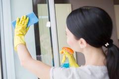 Brunette säubert das Glas des Fensters mit blauem Lappen- und Flüssigkeitsspray Sie tut es vorsichtig lizenzfreies stockfoto