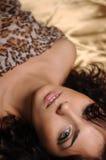 Brunette s'étendant sur une soie d'or Photo stock