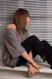 Brunette s'asseyant sur l'hublot Images libres de droits