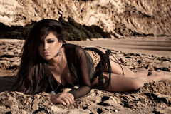 Brunette In The Sand. Gorgeous brunette laying in the warm sand in the beach Stock Photography