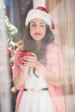 Brunette in santa hat holding mug Stock Image