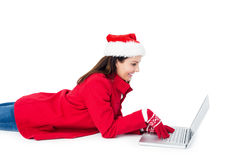 Brunette with santa hat lying on the floor using her laptop Royalty Free Stock Photo
