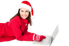 Brunette with santa hat lying on the floor using her laptop Stock Photo