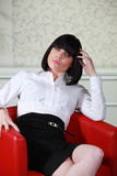 Brunette sat in red chair Royalty Free Stock Image