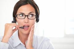 Brunette secretary talking on her headset Stock Images