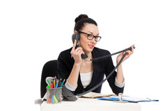 Brunette secretary talking on the phone sitting over table Stock Photography