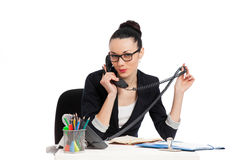 Brunette secretary talking on the phone sitting over table Stock Photos