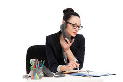 Brunette secretary talking on the phone sitting over table Stock Images