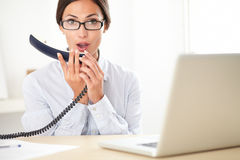 Brunette secretary talking to the phone Royalty Free Stock Photos