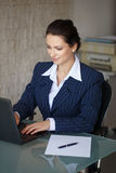 Brunette secretary typing letter on laptop Stock Image