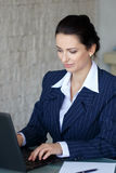Brunette secretary typing letter on laptop Stock Images