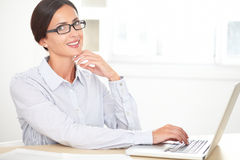 Brunette secretary using her laptop on desk Stock Images