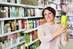 Brunette selecting bottle of shampoo Stock Photography