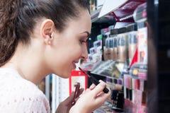 Brunette selecting lip gloss Stock Images