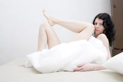 Brunette serious woman lying on bed cover blanket Stock Photo