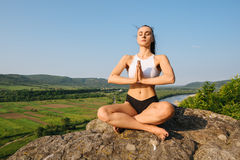 Brunette sexy athletic woman with muscular body practicing yoga on the rock. Blue sky background. Royalty Free Stock Images