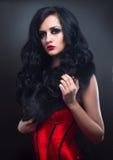 Brunette sexy dans la fourrure rouge de corset et le long cheveu dans s Photos libres de droits