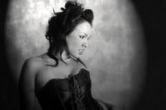 Brunette sexy dans le spotlit de corset. photographie stock libre de droits