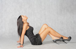 Brunette in dress sitting on a floor and looking up Stock Photo