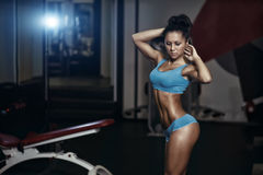 Brunette fitness girl posing in the gy. Brunette fitness girl in blue sport wear with perfect body in the gym posing before training set Royalty Free Stock Photo