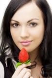 Brunette sexy, qui mange des fraises photo stock