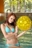 Brunette retenant une bille de plage jaune de point de poka Photo stock