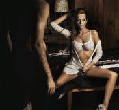 brunette sexy s'asseyant sur le bâti Photo libre de droits