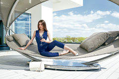 Brunette sexy woman glamour fashion luxury life style lady sit on stylish hammock modern interior building house party time drink Stock Photo
