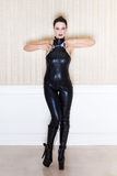 Brunette sexy woman in latex catsuit showing handcuffs Stock Photo