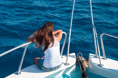 Woman on shipboard of yacht. Brunette on shipboard of yacht with legs out. Copyspace Royalty Free Stock Photos