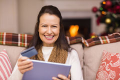 Brunette shopping online with laptop at christmas Stock Photography