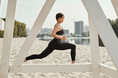 Brunette with short haircut does stretching on river beach Stock Photos