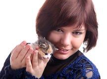 Brunette short-haired girl in lace dress holds kitten Stock Photos