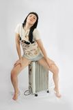 Brunette in shorts sits on heater Royalty Free Stock Images