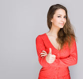 Brunette showing big thumbs up. Portrait of a cute young brunette showing big thumbs up stock image