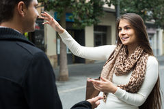 Brunette showing direction to Indian guy at the street Stock Images
