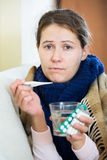 Brunette sick with fever under blanket in domestic interior Stock Photos