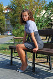 Brunette sits on bench. Royalty Free Stock Images