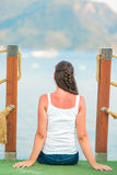 Brunette sits on the edge of the pier Stock Images