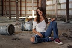 Brunette Sitting in Abandoned Warehouse (2) stock photography