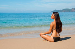 Brunette sitting on the beach in a lotus position Royalty Free Stock Photo